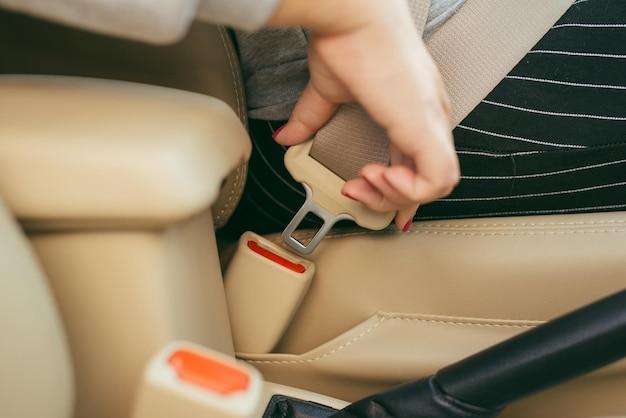 차에 앉아 안전벨트를 매는 여성의 자른 이미지