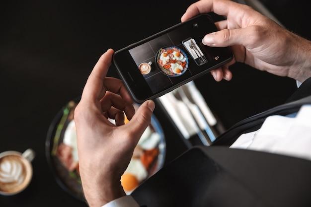カフェに座っている青年実業家のトリミング画像は、携帯電話で食べ物の写真を撮ります。
