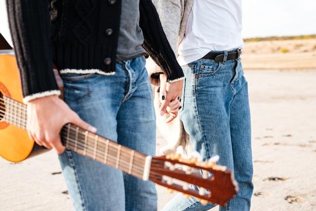 기타와 함께 걷고 해변에서 손을 잡고 젊은 캐주얼 커플의 자른 이미지