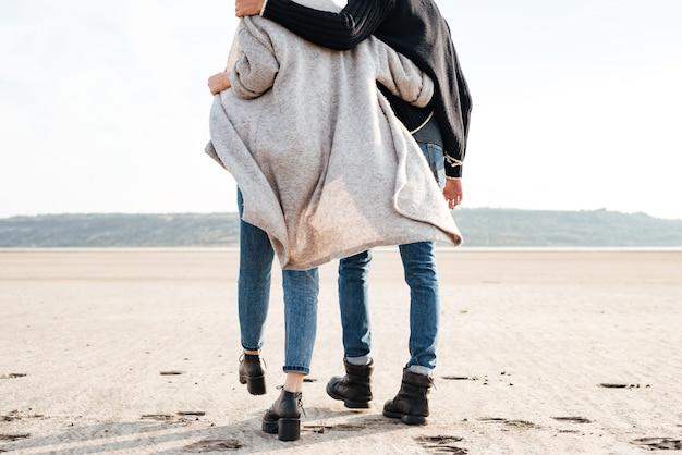 海岸沿いを歩いているカジュアルな服を着た若いカップルのトリミングされた画像