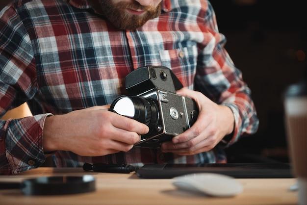 Обрезанное изображение молодого инженера, фиксирующего старинную камеру, сидя на своем рабочем месте