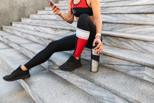 Обрезанное изображение молодой спортсменки, держащей мобильный телефон, слушающей музыку в наушниках, питьевой водой