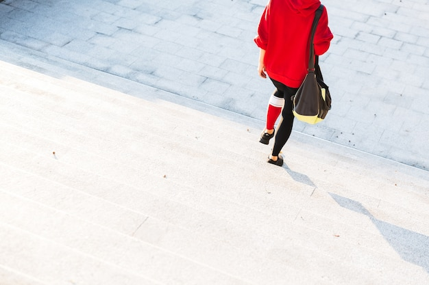 야외에서 걷는 까마귀를 입고 스포츠 가방을 들고 젊은 운동가의 자른 이미지