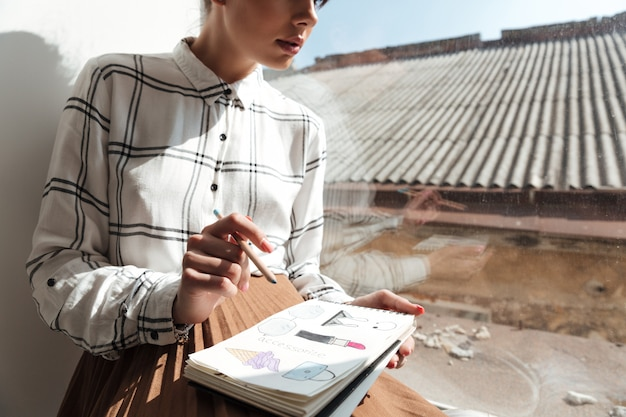 Обрезанное изображение молодой женщины художника рисования эскизов