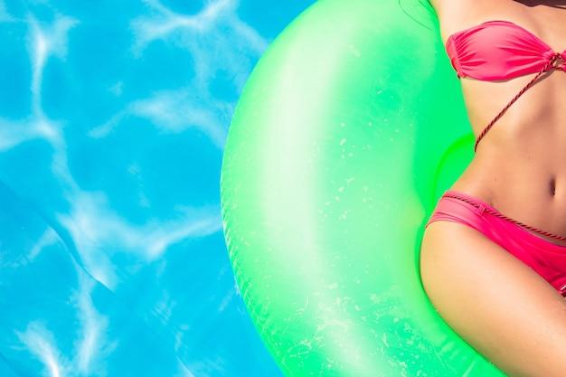 Обрезанное изображение молодой женщины, лежащей на надувном матрасе в бассейне