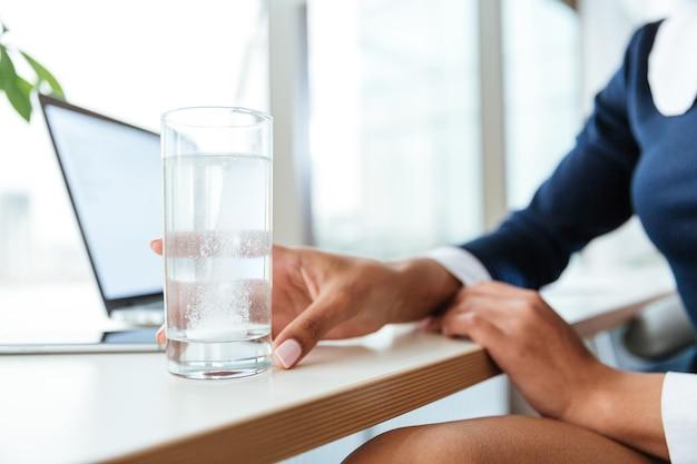 ドレスを着たアフロビジネスウーマンのトリミングされた画像は、オフィスで一杯の水と丸薬とテーブルのそばに座っています。カップに焦点を当てる