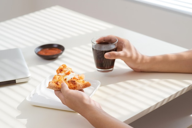 彼の机で働いている間ピザと一緒に昼食をとっているアジア人男性のトリミングされた画像。