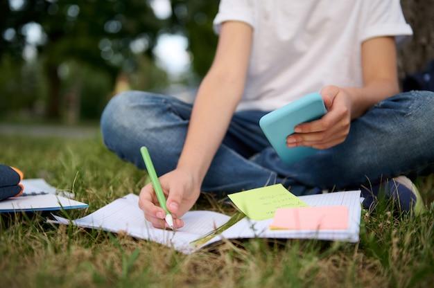 Обрезанное изображение до неузнаваемости школьника, который учится в парке, сидит на зеленой траве и решает математическую задачу, используя смартфон и мобильные приложения, делая заметки в тетради и рабочей тетради.