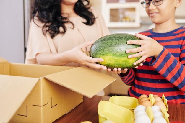 Обрезанное изображение азиатских матери и сына, берущих свежий арбуз, который они заказали онлайн из картонной коробки