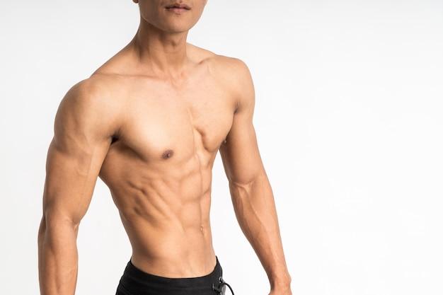 Обрезанное изображение азиатского молодого человека, показывающего мускулистый живот, стоящий лицом к стороне