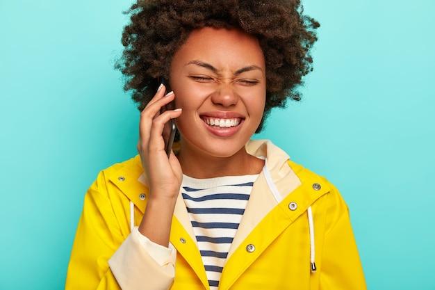 Обрезанное изображение привлекательной темнокожей женщины с афро-волосами, смеющейся над забавной историей друзей, держащей сотовый телефон, одетой в желтый плащ