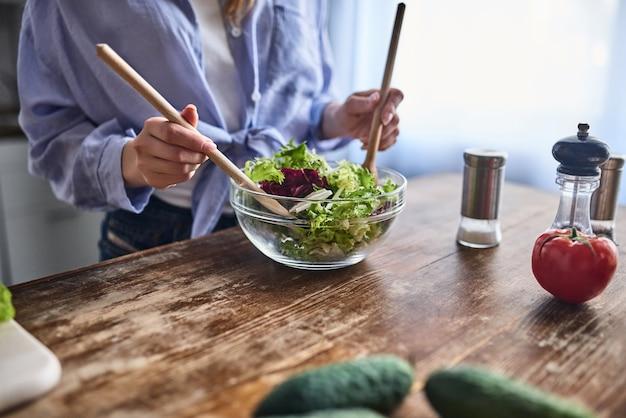 魅力的な若い女性のトリミングされた画像は、キッチンで料理しています。サラダ作り。健康的なライフスタイルのコンセプト。