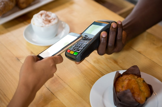 カフェで携帯電話で支払いを受け付けているバリスタのトリミング画像