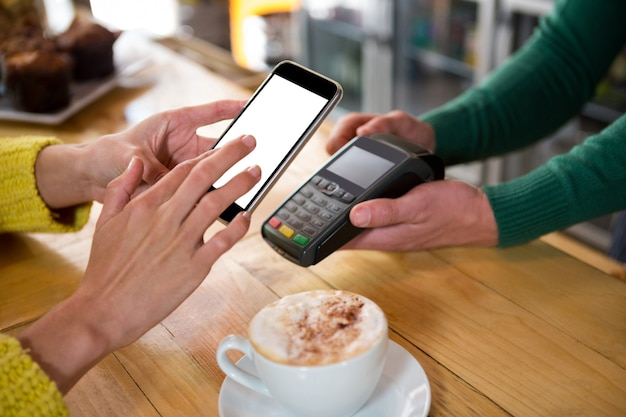 カフェでスマートフォンで支払いを受け入れるバリスタのトリミング画像