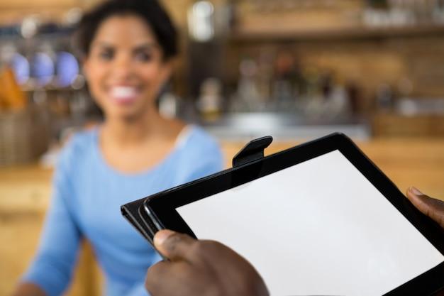 カフェでバックグラウンドで顧客とデジタルタブレットを保持しているバリスタの手のトリミングされた画像