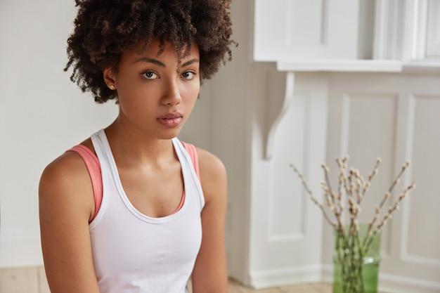 Обрезанное изображение красивой женщины с вьющимися волосами, здоровой темной кожей, одетой в повседневную белую футболку, серьезно смотрит прямо в камеру.