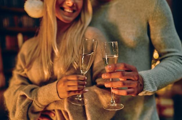 Обрезанное изображение красивой молодой пары в шляпах санты держит бокалы шампанского и улыбается во время празднования нового года у себя дома.
