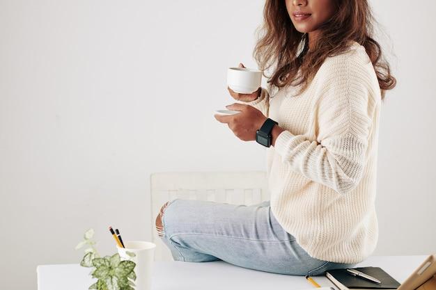 Обрезанное изображение красивой молодой женщины, сидящей на столе с чашкой кофе, наслаждаясь коротким перерывом между онлайн-встречами