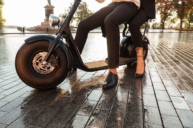 현대 오토바이에 앉아 비즈니스 커플의 이미지를 자른