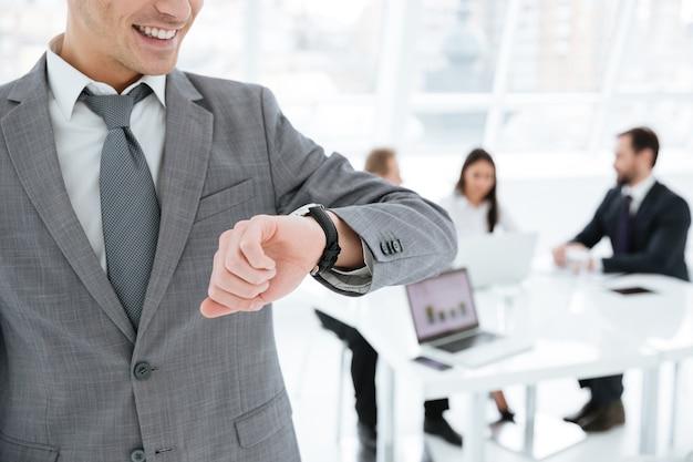 オフィスで同僚と腕時計を見ているビジネスマンのトリミングされた画像