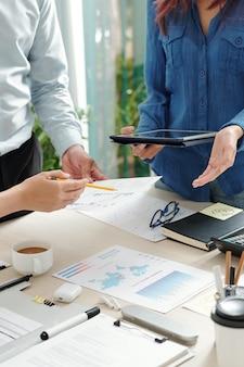 회의에서 다양한 차트와 보고서를 확인하고 비즈니스 비용을 논의하는 비즈니스 사람들의 자른 이미지