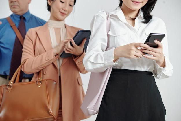 대기열에 서서 스마트폰에서 모바일 애플리케이션을 사용하는 비즈니스 사람들의 자른 이미지