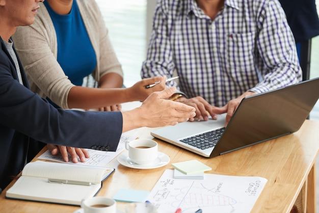 朝の会議でラップトップでのプレゼンテーションを議論しているビジネスチームのトリミングされた画像