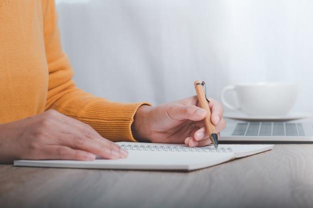 테이블에 앉아 노트북에 메모를하는 비즈니스 우먼의 자른 이미지