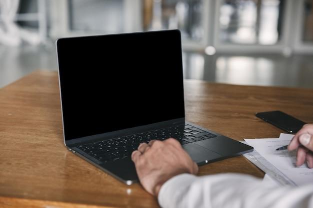흰색 셔츠와 검은 색 정장을 입고 사무실에서 테이블에 앉아 노트북의 copyspace 화면을보고, 문서 작업 중에 비즈니스 다운 남자의 자른 이미지