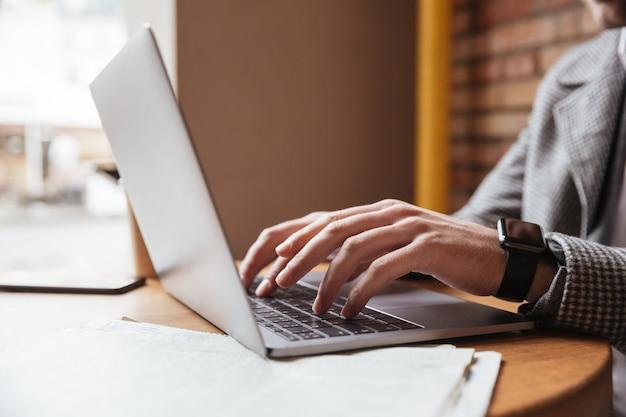 カフェのテーブルのそばに座ってラップトップコンピューターを使用して眼鏡のビジネスマンの画像をトリミング