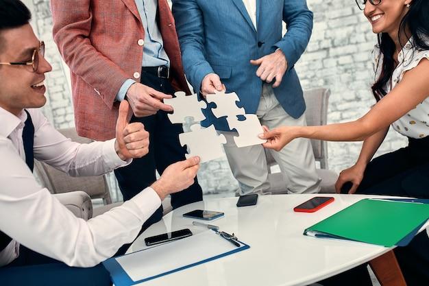 Обрезанное изображение бизнесменов, соединяющих кусочки головоломки в офисе