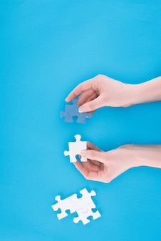 Cropped image of businesswoman assembling blue and white puzzles isolated on blue, busines