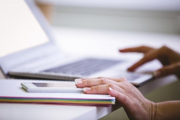 Обрезанное изображение бизнес-леди с мобильным телефоном при использовании ноутбука в офисе