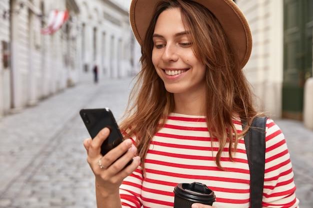 Обрезанное изображение очаровательной туристки использует приложение на сотовом телефоне