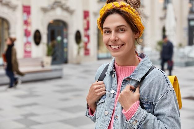 쾌활한 젊은 백인 여자의 자른 이미지는 작은 배낭과 함께 도시를 산책하고 노란색 머리띠와 데님 재킷을 입고