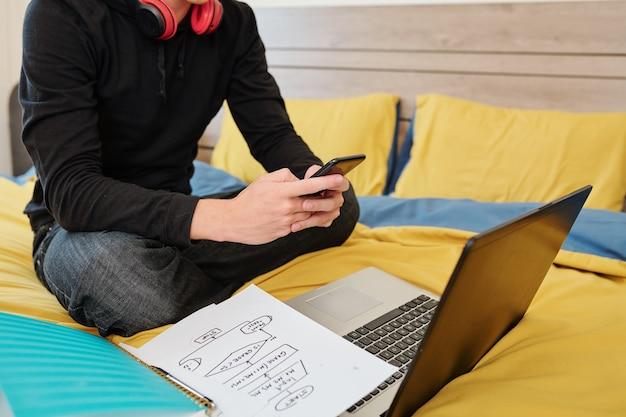 Обрезанное изображение студента колледжа, сидящего на кровати и фотографирующего блок-схему, которую он нарисовал во время онлайн-урока