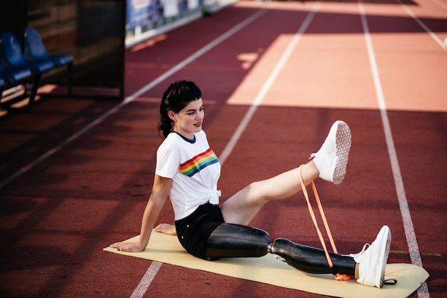 ビーチに座ってストレッチ体操を行う義足の集中障害者アスリート女性の画像をトリミング