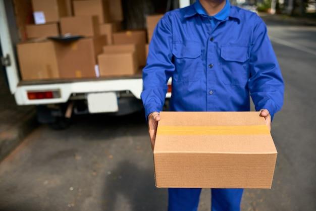 顧客に小包を配達する制服を着た宅配便のトリミングされた画像、彼のバンは背景にあります