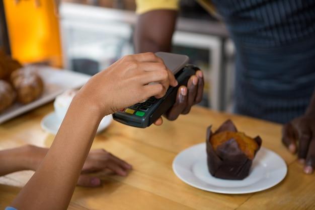 コーヒーショップでスマートフォンを介してバリスタを支払う顧客のトリミングされた画像