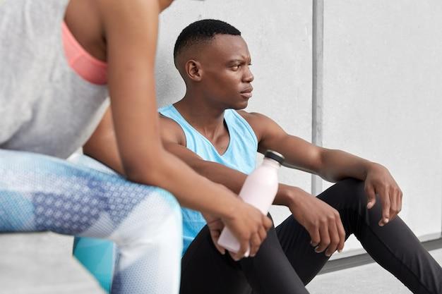 黒い肌の男性のトリミングされた画像は疲れて座っています、彼のパートナーは冷たい水のボトルで近くにポーズをとり、一緒にスポーツをし、アクティブなライフスタイルをリードし、ジムや屋外で定期的なトレーニングを受け、スポーツ服を着ています