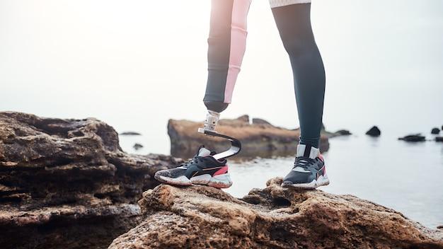 バイオニック脚を持つスポーツウェアの障害のある若い女性のトリミングされた画像