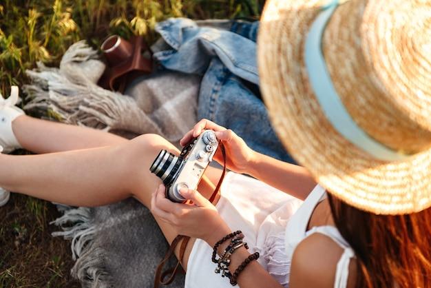 Обрезанное изображение европейской женщины в соломенной шляпе, держащей ретро-камеру, сидя на траве в летнем парке