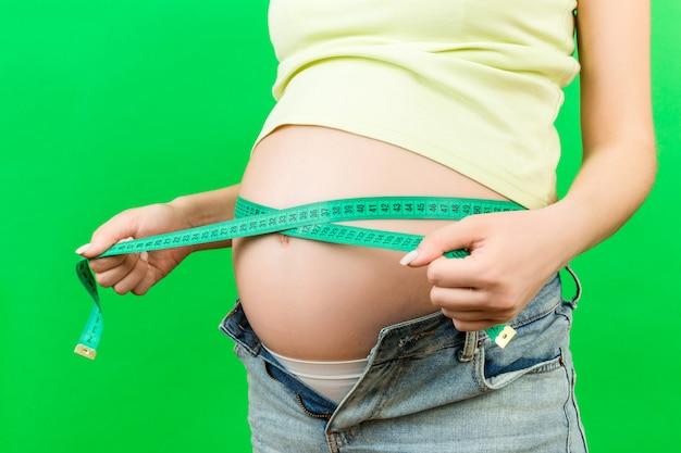화려한 배경에서 줄자를 가진 그녀의 임신 배꼽을 측정 압축이 풀린 된 청바지에 기대 어머니의 자른 된 이미지. 엔티 미터 측정