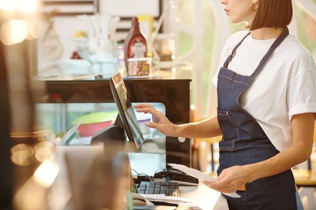 Обрезанное изображение женщины-бариста, работающей в кафе и использующей кассовый аппарат при приеме оплаты или вводе деталей заказа.
