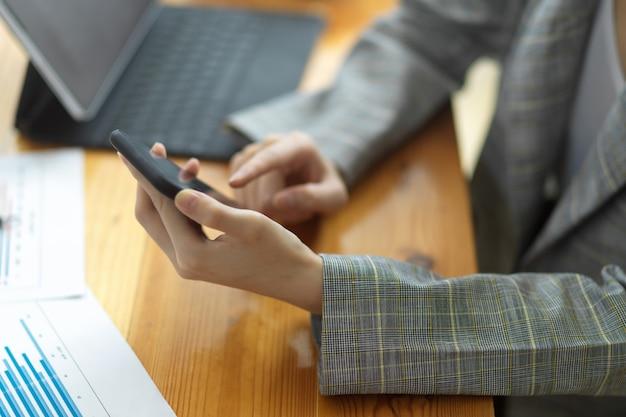 Обрезанное изображение женщины-предпринимателя или деловой женщины, просматривающей интернет через смартфон на своем столе. текстовое электронное письмо для переговоров с бизнес-клиентами. работаю на мобильном телефоне