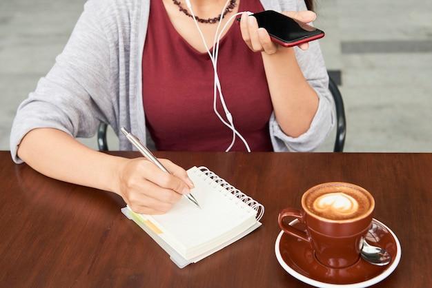 동료를위한 음성 메시지를 녹음하고 카페 테이블에 앉아 플래너에 메모를하는 여성 기업가의 자른 이미지