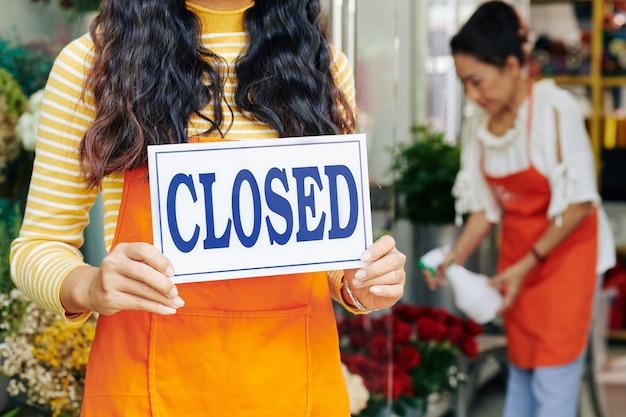 閉じたサインを保持している女性の花屋のオーナーのトリミングされた画像