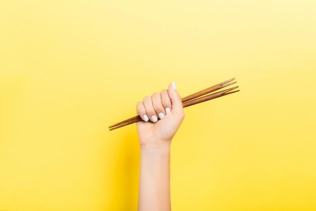 Подрезанное изображение женской руки держа палочки в кулаке на желтой предпосылке. азиатская еда концепция с копией пространства