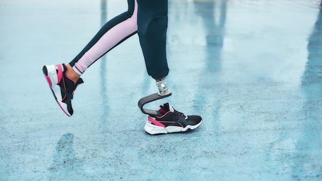Обрезанное изображение женских ног с протезом на прогулке на открытом воздухе