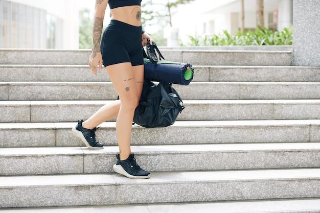 손에 체육관 가방과 함께 계단을 걷고 반바지와 스포츠 브래지어에 맞는 젊은 여자의 자른 이미지